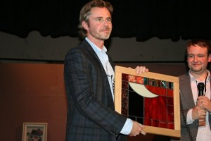 Sam receives an orginal piece of stained glass art as a thank you.