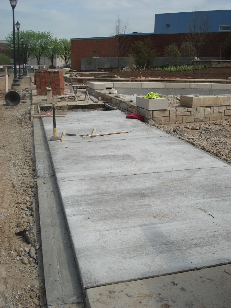 Parts of the inner sidewalk has been formed and poured and the stone capping continues to be installed around the reflecting pool.